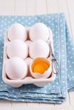 6 свежих яичек в держателе яичка с одним треснули яичко Стоковое Фото