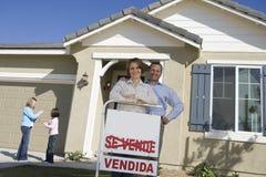 中间成人夫妇画象在新房孩子(6-9)前面的在背景中 库存照片