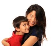 6 años que abrazan a la mama Imagen de archivo libre de regalías