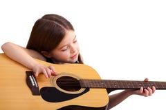 6 anos de jogos velhos da menina na guitarra Imagem de Stock