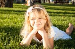 6 anos de menina idosa que relaxa no prado Imagem de Stock Royalty Free