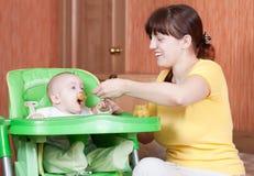 6 behandla som ett barn mata henne månadmodern Fotografering för Bildbyråer