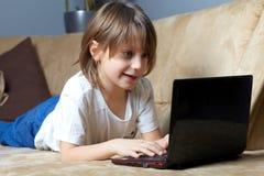 6 Einjahresjunge, der auf dem Sofa mit seinem Laptop liegt Lizenzfreie Stockfotos