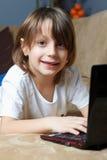 6 Einjahresjunge, der auf dem Sofa mit seinem Laptop liegt Stockfotos