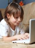 6 Einjahresjunge, der auf dem Sofa mit seinem Laptop liegt Lizenzfreies Stockbild