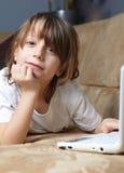 6 Einjahresjunge, der auf dem Sofa mit seinem Laptop liegt Stockfotografie