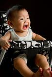 6-Monats-altes asiatisches Baby, das im hohen Stuhl schreit Lizenzfreies Stockfoto