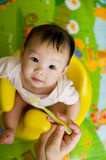 6 month old Asian baby girl being fed cereal. While sitting in a yellow seat Royalty Free Stock Images