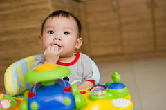 6 month old Asian baby girl chewing fingers. 6 month old Asian baby girl chewing her fingers while sitting in a walker Royalty Free Stock Photography