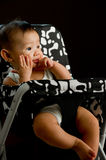6 month old Asian baby girl chewing fingers. 6 month old Asian baby girl chewing her fingers while sitting in high chair Stock Images