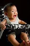6 month old Asian baby girl crying in high chair. With black background Royalty Free Stock Photo
