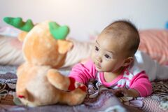 Free 6 Month Old Asian Baby Girl Is Smiling, Enjoying His Doll Stock Photo - 179168410
