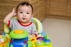6 month old Asian baby girl smiling excitedly. While sitting in a walker Royalty Free Stock Image
