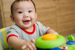 6 month old Asian baby girl smiling excitedly. While sitting in a walker Royalty Free Stock Photo