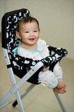 6 month old Asian baby girl smiling sweetly. While sitting in a high chair Stock Photography