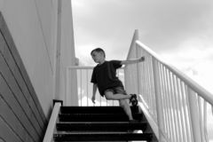6 year old boy. Little 6 year old boy playing in the stairs stock photo