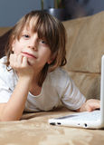 6 year old boy lying on the sofa with his laptop Stock Photography
