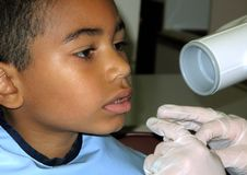 6 year old multiracial boy at dentist checkup. 6 year old multiracial boy in dentist chair getting trained on what to do during x ray at an annual check up with Royalty Free Stock Photos