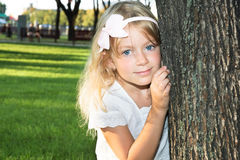 6 years old girl playing at park behind a tree Stock Image