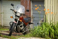 60s,70s,80s. An old fashioned motorcycle at backyard royalty free stock image