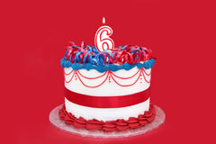 6th Cake. Cake with number six numeral candle, on vibrant red background Stock Photo