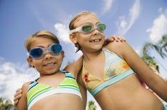 两个女孩(7-9)游泳衣画象的。 免版税库存图片