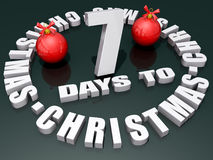 7 Days to Christmas. The words 7 Days to Christmas on a shiny green background with two red ornaments Stock Photo