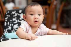 7 month old Asian baby girl. Sitting in her high chair at the dining table Stock Photos