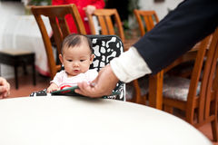 7 month old Asian baby girl, holding the menu Royalty Free Stock Images