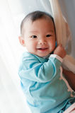 7 month old Asian baby girl smiling and holding on. To a curtain, wearing blue Royalty Free Stock Photo