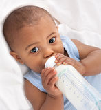 7-month old baby holding milk bottle Stock Images