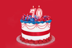 70th Cake. With numeral candles, on vibrant red background Stock Photos