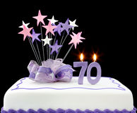 70th Cake. Fancy cake with number 70 candles.  Decorated with ribbons and star-shapes, in pastel tones on black background Stock Photos