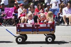 小女孩在一点红色无盖货车,游行7月4日,美国独立日,碲化物,科罗拉多,美国挥动 免版税图库摄影