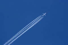 747 in air. Flight of Boeing 747 on clear blue sky with white trails behind Stock Photo