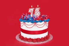 75th Cake. With numeral candles, on vibrant red background Stock Photo