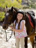 拿着小的小马马微笑的愉快的佩带的安全骑师盔甲的辔女孩7或8岁在暑假 图库摄影