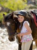 拿着小的小马马微笑的愉快的佩带的安全骑师盔甲的辔女孩7或8岁在暑假 库存图片