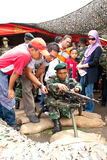 78th Malaysian Army Anniversary Celebrations 2011. KUALA LUMPUR, MALAYSIA-MAR 5:Unidentified soldier brief visitor on weapon at the 78th Army Anniversary on Mar Stock Image