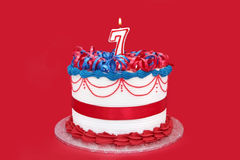 7th Cake. Cake with numeral seven candle, with vibrant red background Stock Images