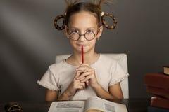 8 années de fille avec des livres i Photographie stock libre de droits