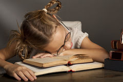 8 anos de menina idosa estão dormindo no livro Foto de Stock