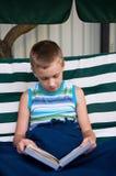 8-Jähriges Schülerlesebuch draußen Stockbild