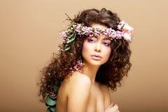 8 mars. Springtime. Skönhetkvinna med kranen av blommor över beige Royaltyfri Fotografi