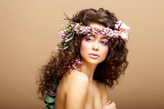 8 Marzec. Wiosna. Piękno kobieta z wiankiem kwiaty nad beżem Fotografia Royalty Free