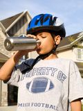 8 year old African American boy drinking water. 8 year old African American boy in bike helmet, drinking from reusable steel water canister Stock Images