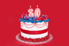 80th Cake. With numeral candles, on vibrant red background Stock Images