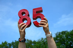 85th Birthday Numbers in Sky. A woman is holding up the numbers eight and five to announce an eighty-fifth birthday stock photos