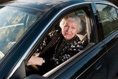 86 éénjarigenvrouw bij haar huis, drivingn haar auto Stock Foto's