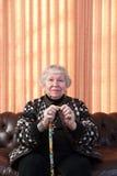 86 Einjahresfrau an ihrem Haus, Stock anhalten Stockfotografie